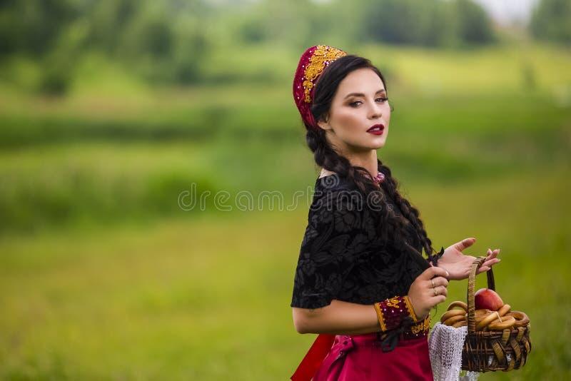 Retrato da forma da morena caucasiano sensual no russo Kokoshnik com a cesta de anéis do pão Levantamento no ar livre do campo da fotografia de stock