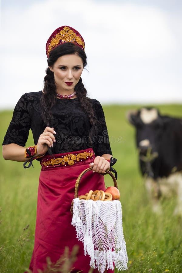 Retrato da forma da morena caucasiano sensual no russo Kokoshnik com a cesta de anéis do pão Levantamento contra o ar livre da va imagens de stock royalty free
