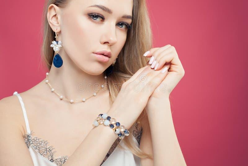 Retrato da forma da mulher atrativa com os brincos de pedra azuis, o bracelete e a colar da corrente com as pérolas no fundo cor- foto de stock