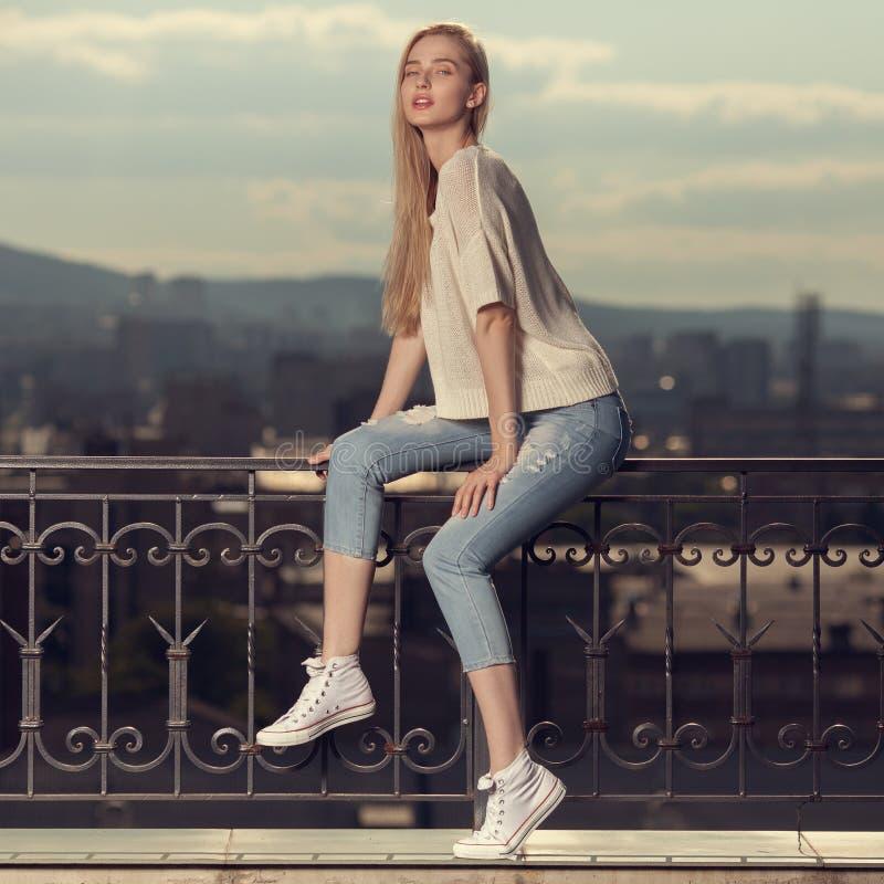 Retrato da forma da mulher loura Calças de brim e sapatilhas fotografia de stock