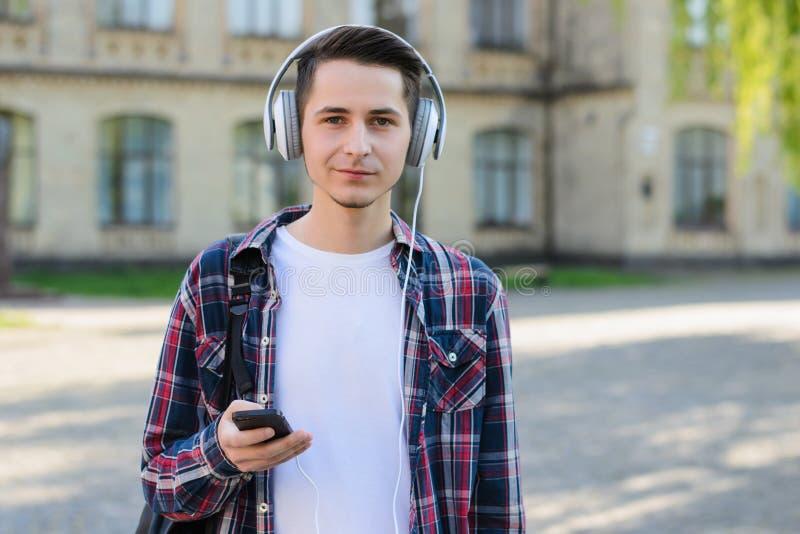 Retrato da foto do close-up do indivíduo considerável satisfeito alegre que usa auriculares para escutar materiais audio em seu t imagens de stock
