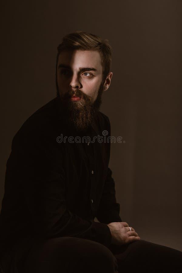 Retrato da foto do Sepia de um homem pensativo com uma barba vestida na camisa preta no fundo branco imagens de stock royalty free