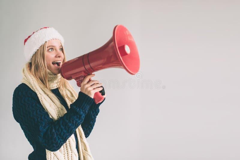 Retrato da gritaria das jovens mulheres usando o megafone sobre a menina do fundo na camisa branca, tiro do estúdio fotos de stock