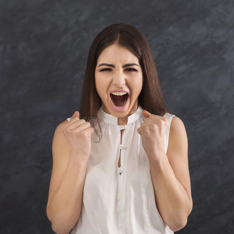 Retrato da gritaria irritada da mulher na câmera imagem de stock