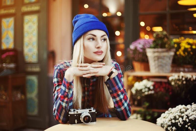 Retrato da jovem mulher à moda bonita que senta-se no café da rua e no café bebendo Moderno com a câmera retro velha imagens de stock