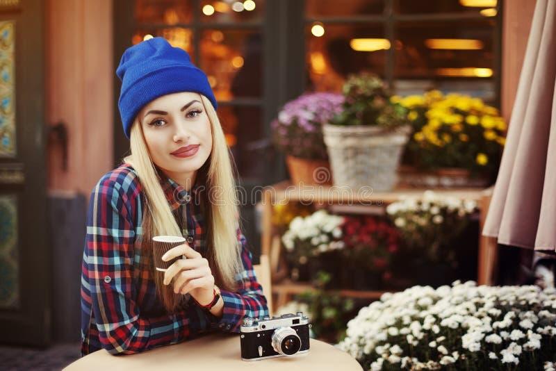 Retrato da jovem mulher à moda bonita que senta-se no café da rua e no café bebendo Moderno com a câmera retro velha fotografia de stock royalty free
