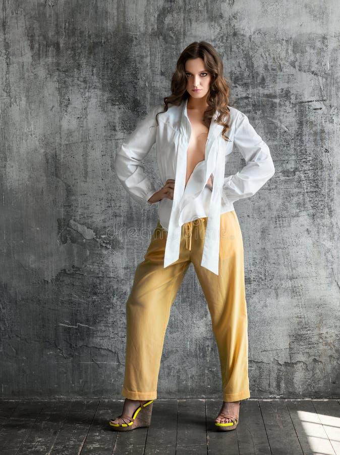 Retrato da jovem mulher à moda na camisa branca e na calças amarela imagem de stock