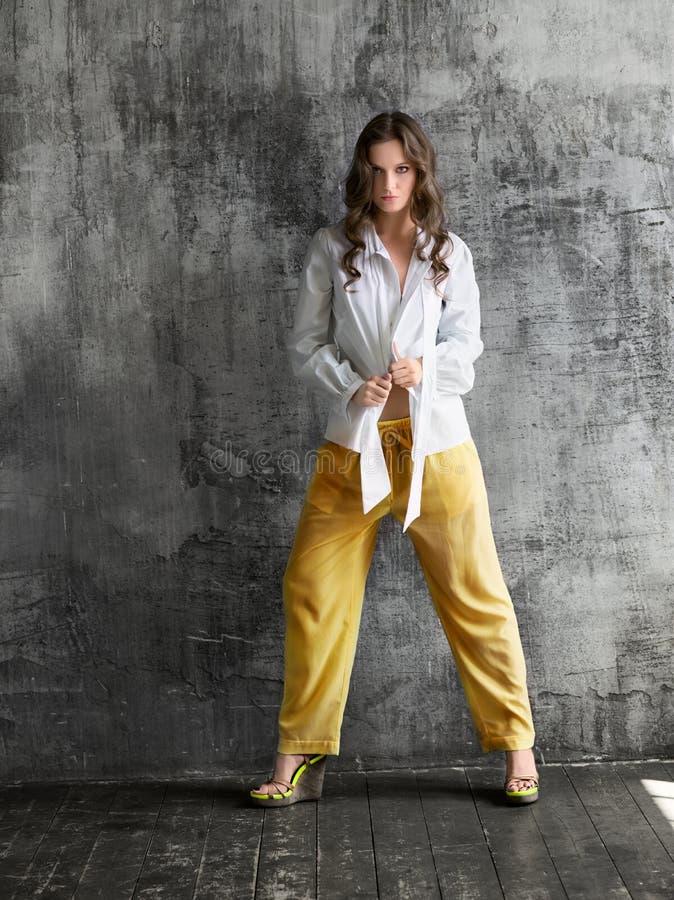 Retrato da jovem mulher à moda na camisa branca e na calças amarela fotografia de stock royalty free