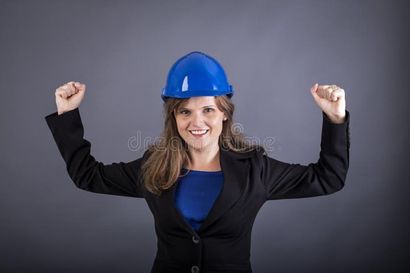 Retrato da jovem mulher alegre com o capacete de segurança com os braços aumentados fotografia de stock royalty free