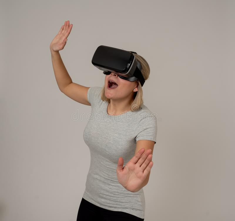 Retrato da jovem mulher alegre e chocada que veste os auriculares da realidade virtual que exploram o mundo 3D imagem de stock