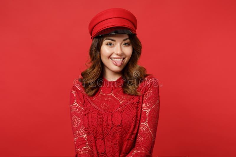 Retrato da jovem mulher alegre engraçada no vestido do laço, tampão que olha a língua da exibição da câmera na parede vermelha br imagens de stock royalty free