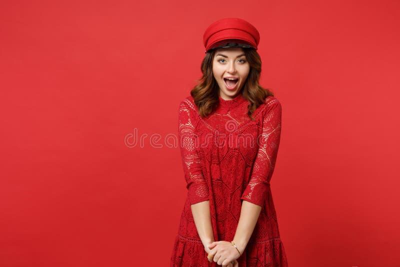 Retrato da jovem mulher alegre entusiasmado no tampão do vestido do laço que mantém a câmera de vista aberta da boca no vermelho  fotos de stock