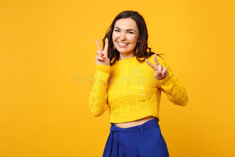 Retrato da jovem mulher alegre na camiseta, calças azul que olha o sinal da vitória da exibição da câmera isolado na laranja amar imagem de stock