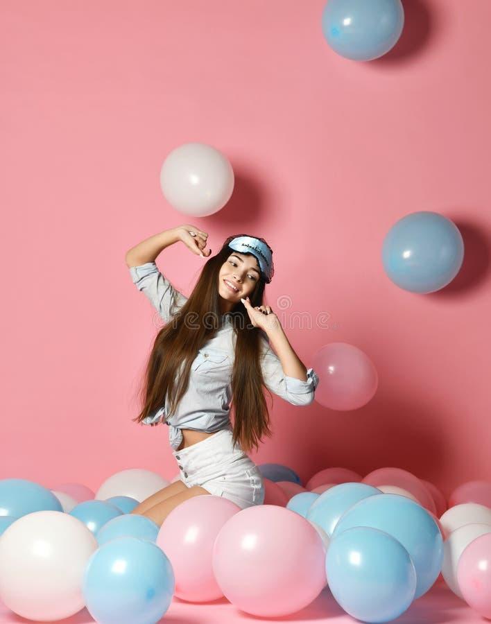 Retrato da jovem mulher alegre na moda que tem muitos balões de ar da cor que olham acima de apreciação ballons no fundo cor-de-r imagens de stock