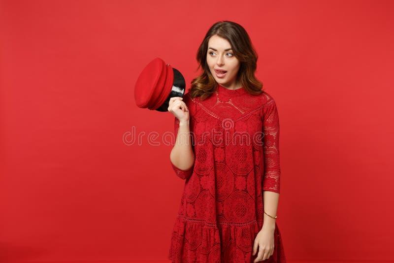 Retrato da jovem mulher alegre no tampão da posse do vestido do laço, olhando de lado, mostrando a língua isolada na parede verme foto de stock