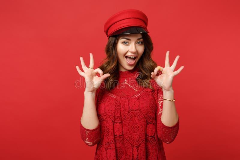 Retrato da jovem mulher alegre no vestido do laço, tampão que olha a câmera, mostrando o gesto APROVADO na parede vermelha brilha imagem de stock