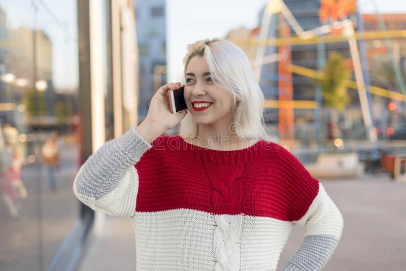 Retrato da jovem mulher alegre que fala no smartphone fora fotografia de stock