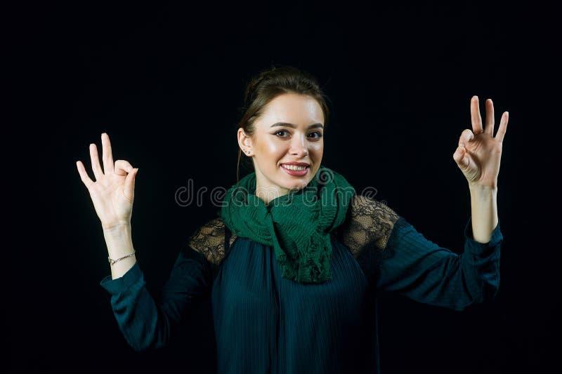 Retrato da jovem mulher alegre que mostra o poço do gesto imagens de stock
