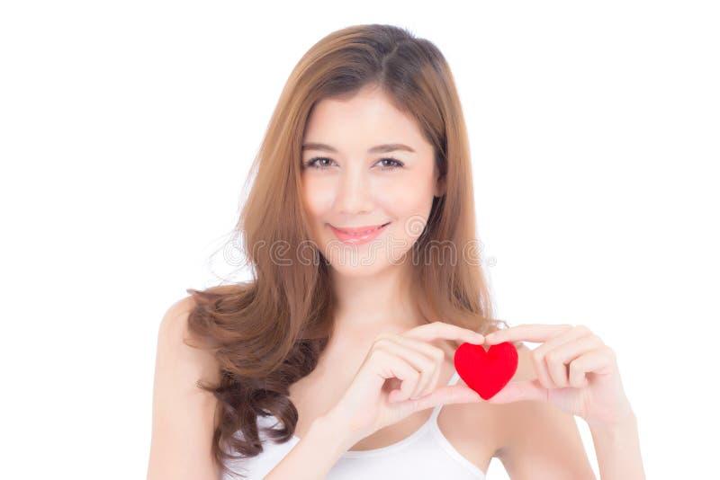 Retrato da jovem mulher asiática bonita que guarda o descanso vermelho e o sorriso da forma do coração isolado no fundo branco fotos de stock