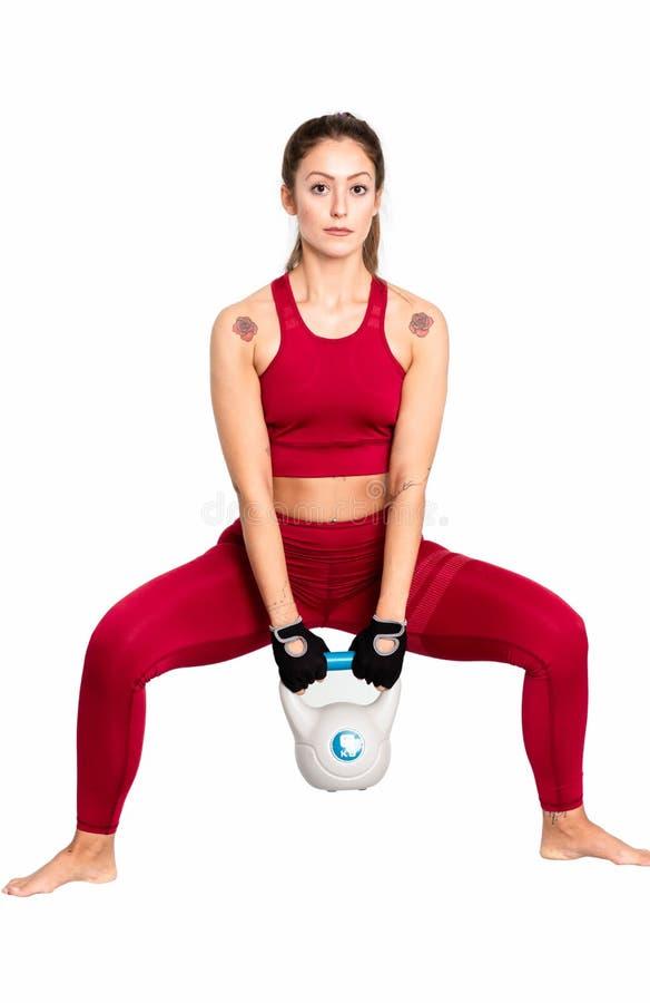 Retrato da jovem mulher atrativa centrado sobre o exercício com kettlebell - imagem fotografia de stock royalty free