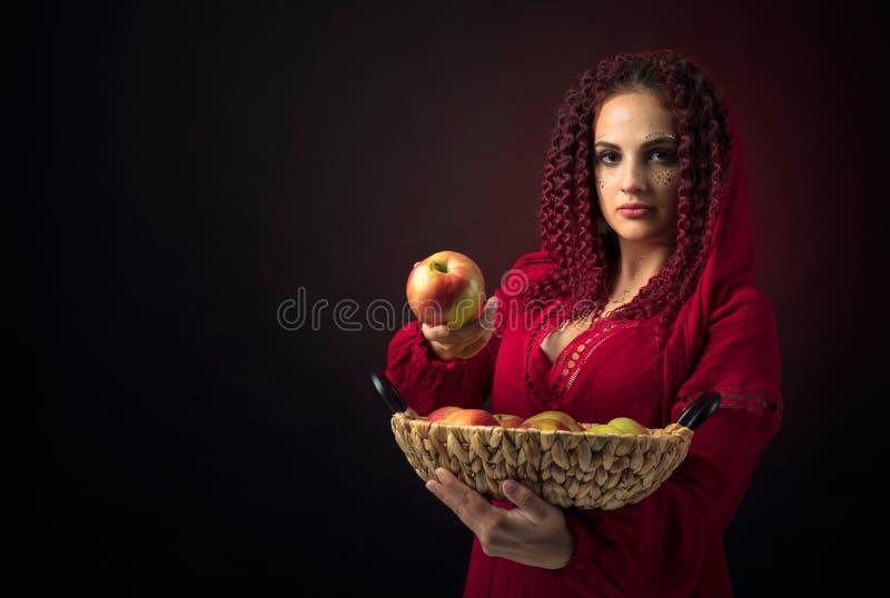 Retrato da jovem mulher atrativa em um vestido vermelho extravagante com a cesta das ma??s fotografia de stock royalty free