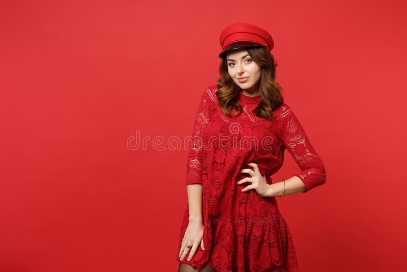 Retrato da jovem mulher atrativa impressionante no vestido do laço, posição do tampão, olhando a câmera isolada na parede vermelh imagens de stock royalty free