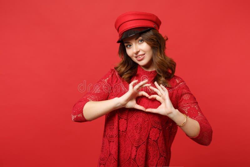 Retrato da jovem mulher atrativa no vestido do laço, tampão que mostra o coração da forma com mãos na parede vermelha brilhante foto de stock