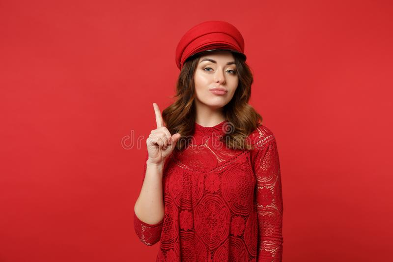 Retrato da jovem mulher atrativa no vestido e no tampão do laço que aponta o indicador acima de olhar a câmera no vermelho brilha fotos de stock