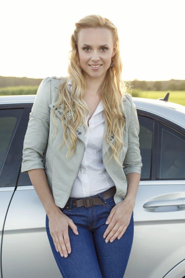 Retrato da jovem mulher atrativa que está pelo carro no campo imagem de stock royalty free
