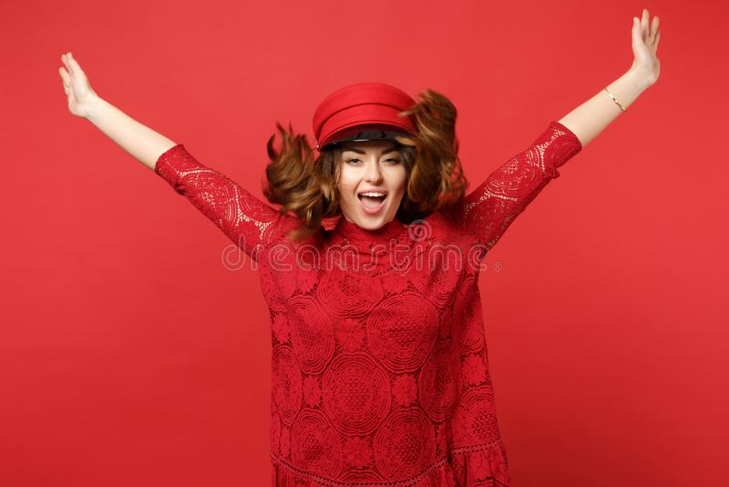 Retrato da jovem mulher bonita alegre no vestido do laço, tampão que salta com mãos de espalhamento na parede vermelha brilhante foto de stock royalty free