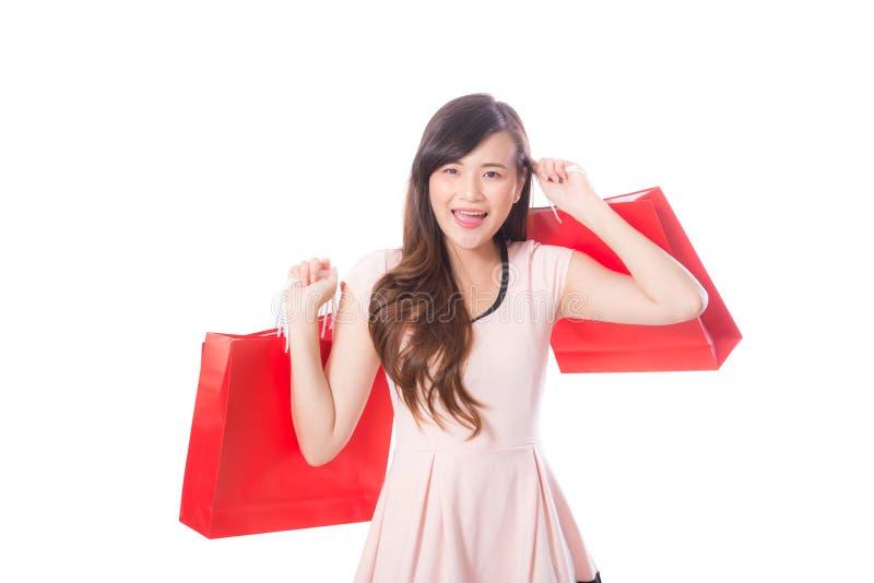 Retrato da jovem mulher bonita asiática que guarda o saco de compras com sorriso e feliz fotografia de stock