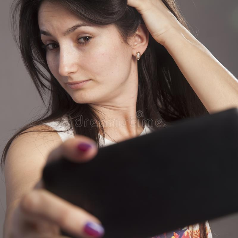 Retrato da jovem mulher bonita atrativa do viciado do selfie Apego, conceito do selfimaniya foto de stock