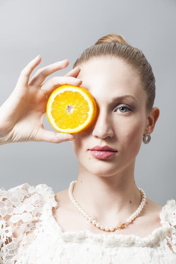 Retrato da jovem mulher bonita com as laranjas no cinza foto de stock