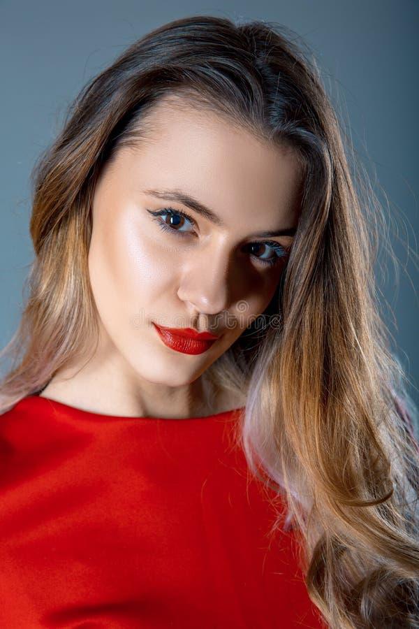 Retrato da jovem mulher bonita com bordos vermelhos e o vestido vermelho no fundo do cinza azul fotografia de stock