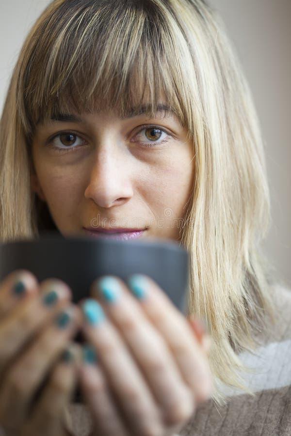 Retrato da jovem mulher bonita com café bebendo imagem de stock