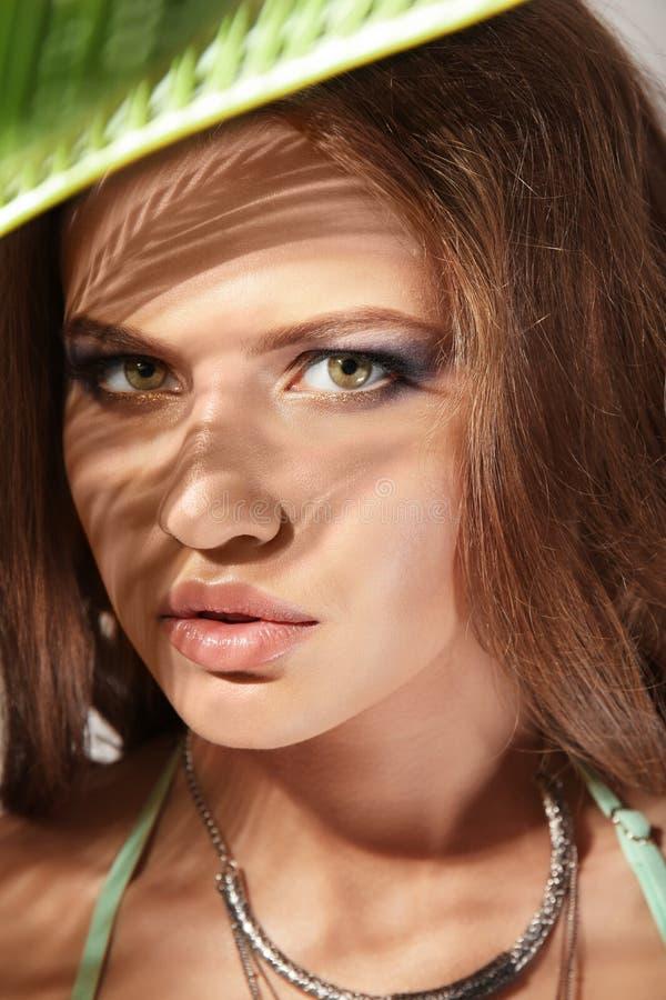 Retrato da jovem mulher bonita com folha de palmeira fotografia de stock royalty free