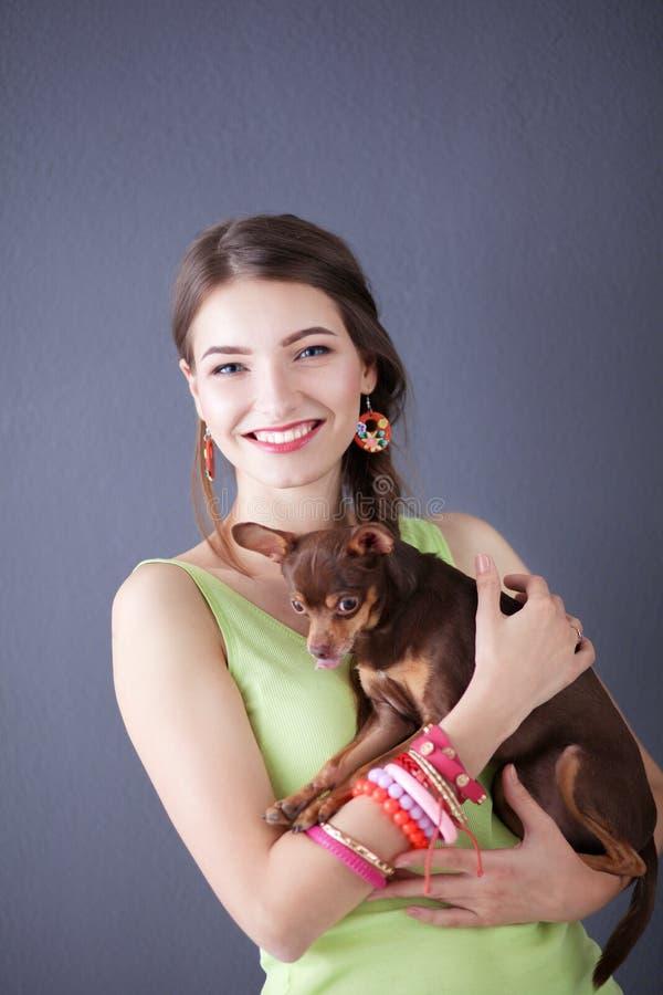Retrato da jovem mulher bonita com o cão no fundo cinzento fotografia de stock royalty free
