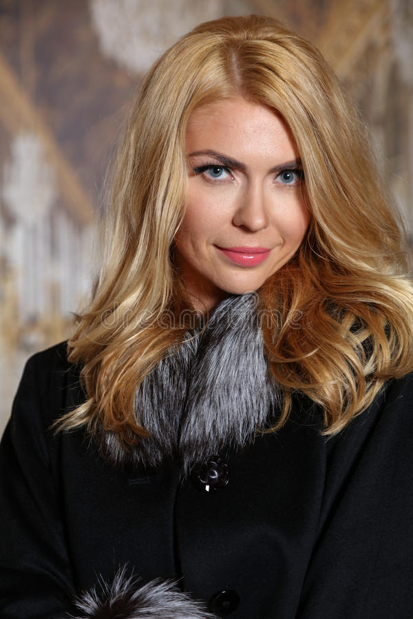 Retrato da jovem mulher bonita com o cabelo louro que veste o casaco de pele elegante que olha a câmera imagem de stock