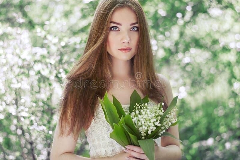 Retrato da jovem mulher bonita com o lírio do vale foto de stock royalty free