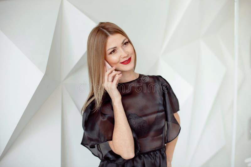 Retrato da jovem mulher bonita com o telefone no fundo interior branco fotografia de stock royalty free