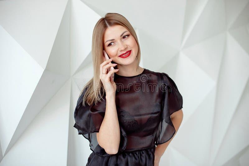 Retrato da jovem mulher bonita com o telefone no fundo interior branco fotos de stock royalty free