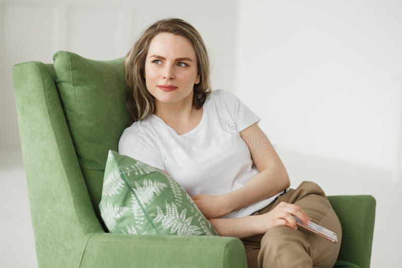 Retrato da jovem mulher bonita com o telefone que senta-se na poltrona na sala de visitas clara fotos de stock