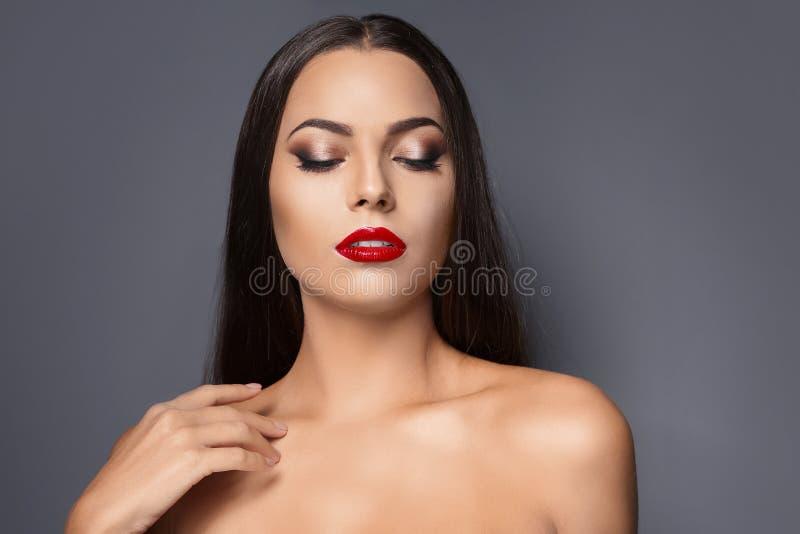 Retrato da jovem mulher bonita com os bordos lustrosos vermelhos foto de stock