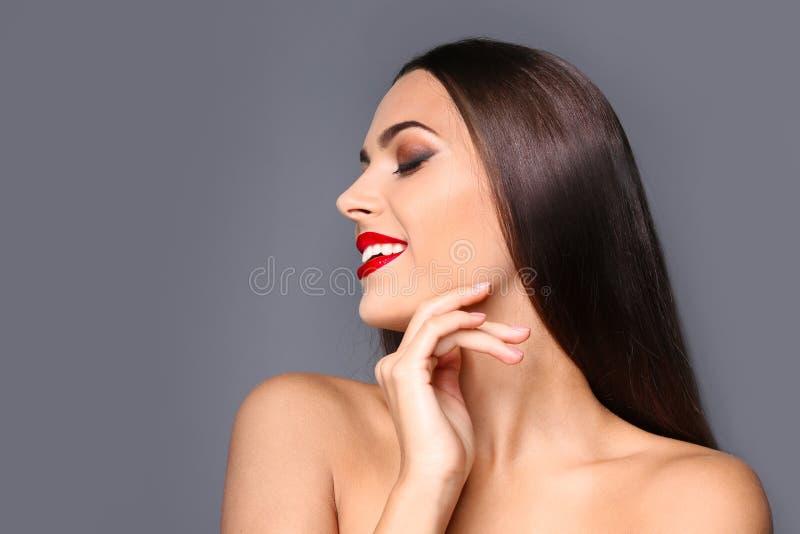 Retrato da jovem mulher bonita com os bordos lustrosos vermelhos fotos de stock royalty free