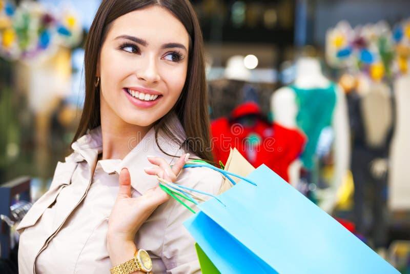 Retrato da jovem mulher bonita com os sacos de compras na roupa imagens de stock royalty free