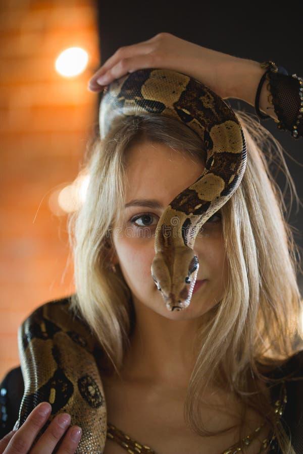 Retrato da jovem mulher bonita com um pitão na cara imagem de stock royalty free