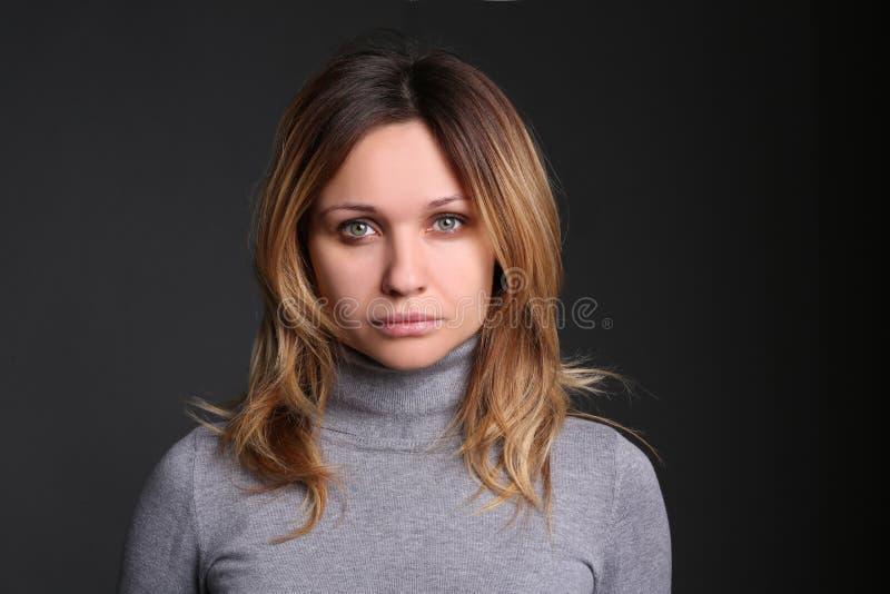 Retrato da jovem mulher bonita contra o fundo preto no estúdio foto de stock