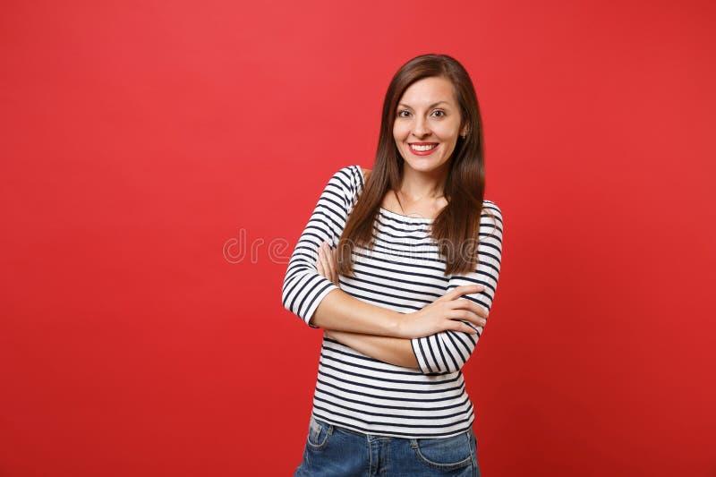 Retrato da jovem mulher bonita de sorriso na posição listrada ocasional da roupa, mantendo as mãos dobradas isoladas no vermelho  imagem de stock royalty free