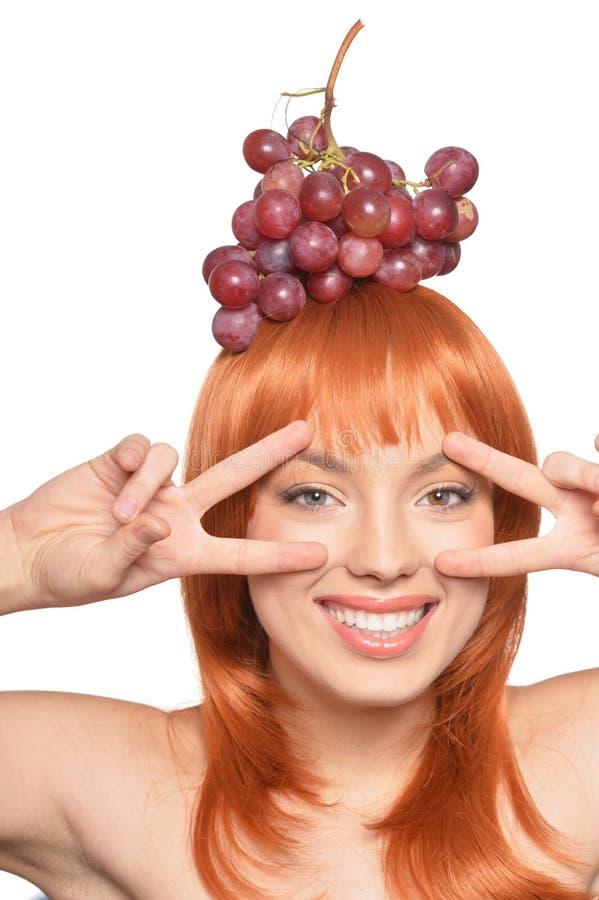 Retrato da jovem mulher bonita do ruivo com as uvas vermelhas na cabe?a que mostra sinais de paz imagens de stock royalty free