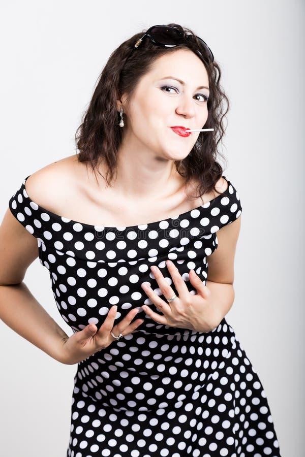 Retrato da jovem mulher bonita feliz que lambe chups do chupa mulher bonita com o pirulito dado forma coração imagens de stock